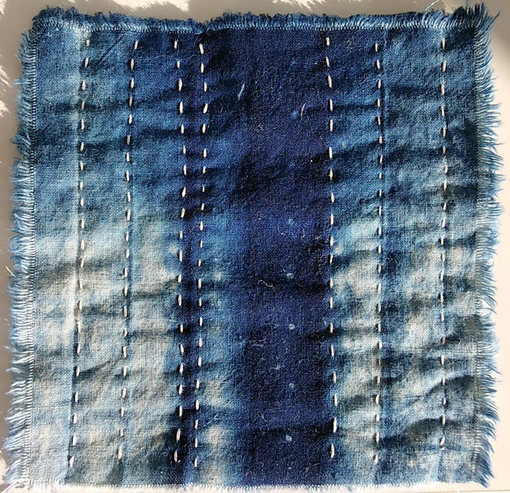 stitch meditation day 1 a blue indigo dyed 5 inch square with white running stitches by doris lovadina-lee
