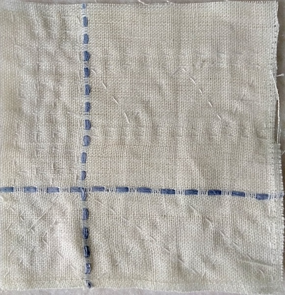 Day 15 stitch meditation of white linen with blue thread in shape of cross stitched in white thread