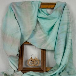 linen rayon soft turquoise scarf draped around wooden frame with smaller frame holding hand crocheted hoop earrings