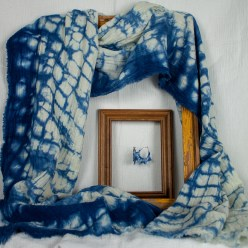 Indigo nui shibori scarf hand dyed draped on frame with indigo earrings