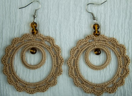 small circle set in a larger circle of beige crochet cotton with brown beads