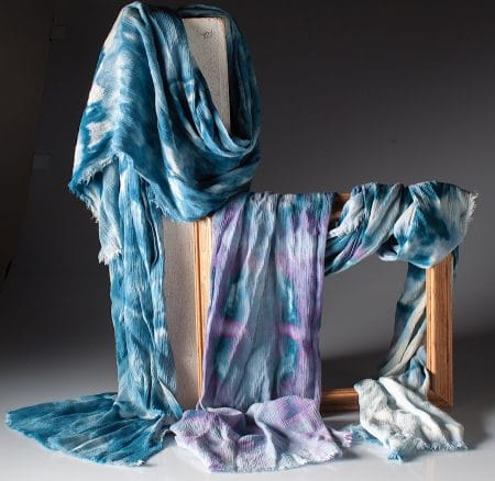 Two snow dyed scarves entwined around a pedestal and wooden frame by Doris Lovadina-Lee Textile Arts