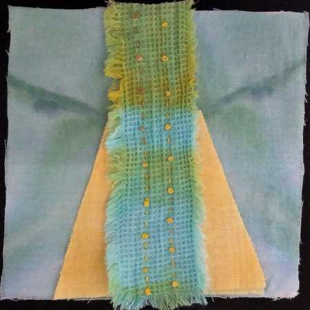 5 inch square hand dyed turquoise cotton with yellow triangle and on top a strip of green and turquoise embroidered with french knots