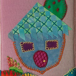 whimsical house embroidered onto a 4x6 inch quilted art postcard