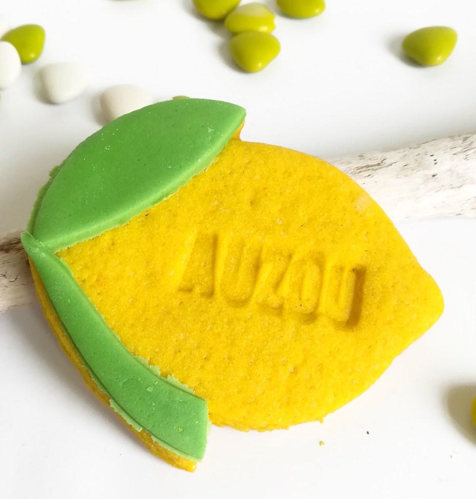Biscuit sablé en forme de citron. Il est personnalisé avec prénom, marque de la société. Couleur jaune et feuille verte.