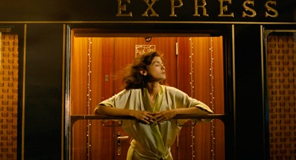 The actress leaning out of a train window in a robe.