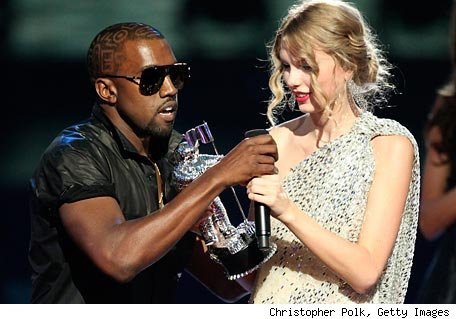 Call the cops!  Kanye is mugging Taylor!