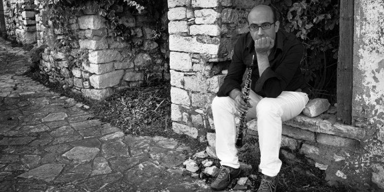 Max Fuschetto seduto su un muretto con l'oboe in mano