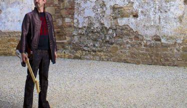Boskovic cantautore con chitarra in piedi davanti a un muro