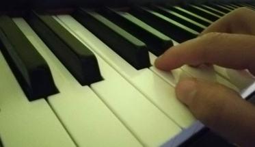 Tasteira del pianoforte con una mano che impara a suonare da autodidatta