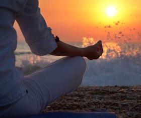 una persona che medita con un tramonto sullo sfondo