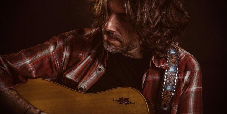 Konrad con la chitarra e una camicia a quadri