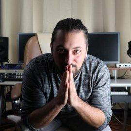 Davide Parola a mani giunte nel suo studio di registrazione