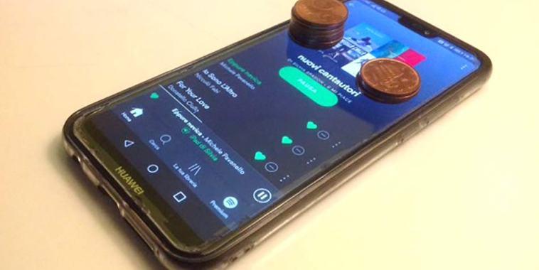 Spotify su un cellulare che fa streaming online e delle monete sullo schermo