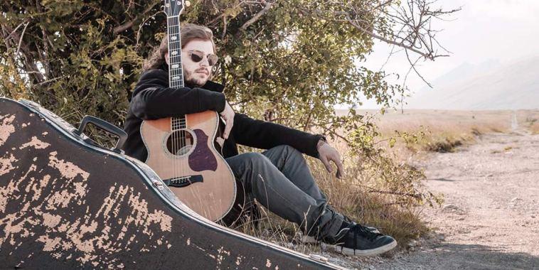 Il chitarrista Daniele Mammarella seduto per terra vicino ad una pianta