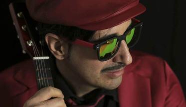 Il cantautore IRonico vestito di rosso con un cappello in testa rosso