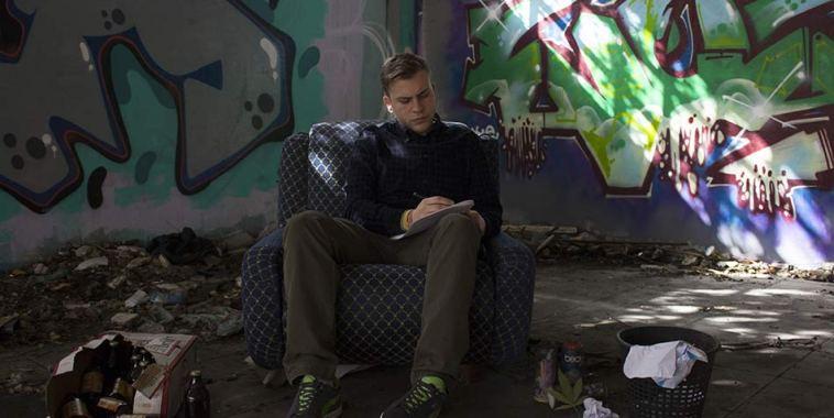 Il cantautore e rapper Vito Five seduto su un divano in una stanza disordinata
