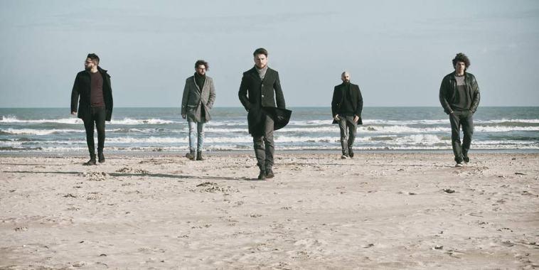 la band La Convalescenza sulla spiaggia con il mare alle spalle