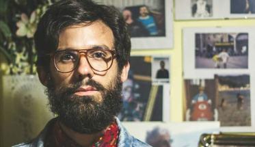 Il cantautore Novamerica davanti ad una parete con delle fotografie appese