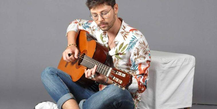 Niccolò Battisti seduco a gambe incrociate con la chitarra