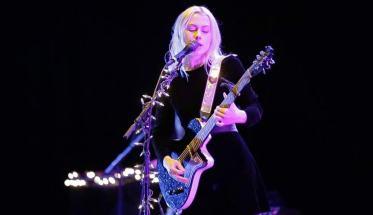 Phoebe Bridgers durante un live con chitarra e microfono