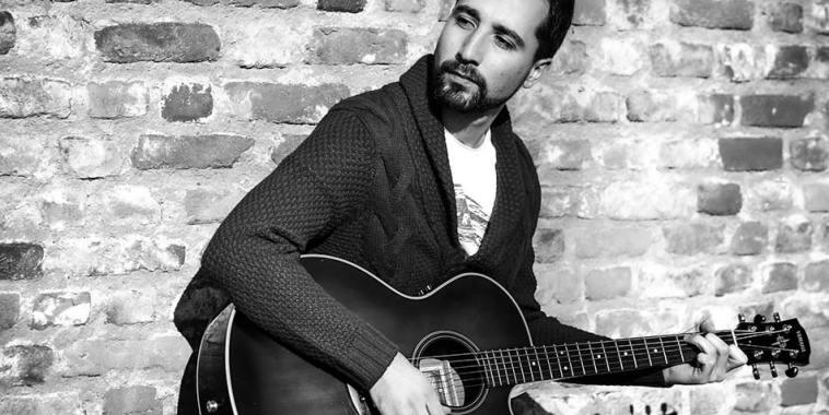Il cantautore INCOMPLETO appoggiato al muro mentre suona la chitarra