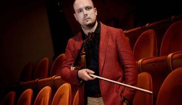 Alessio Bidoli con giacca rossa davanti a potrone rosse di un teatro e sottobraccio il violino, in mano l'archetto