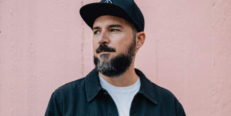 Kose, il rapper con cappellino in testa davanti ad un muro rosa