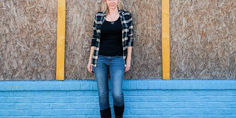Vanessa Peters appoggiata ad un muro di legno