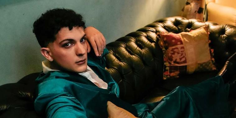 Rosaspina seduto su un divano con una giacca verde acqua