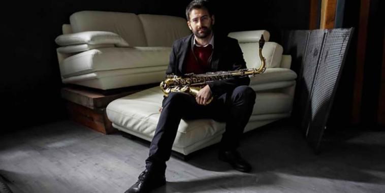 Giovanni Benvenuti con il suo sax, seduto sul divano