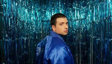 GIACO, Giacomo Prudente con giacca blu su fondo verde acqua