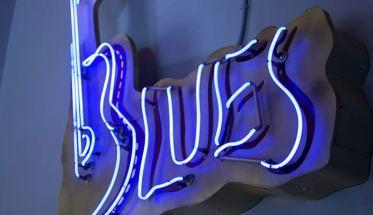 una scritta al neon blu per La Stanza Blues