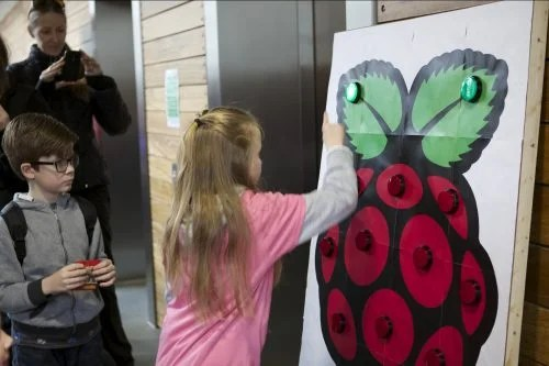 A girl plays a button reaction game at a Raspberry Pi event