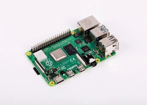 A shiny Raspberry Pi 4 on a flat white surface, viewed at an angle