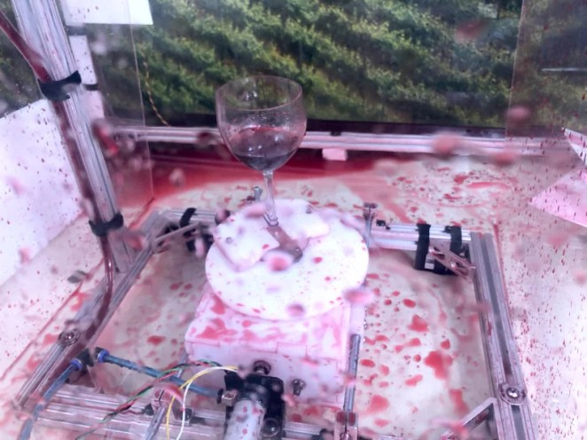 The wine glass spins on a turntable, creating unique splatter art