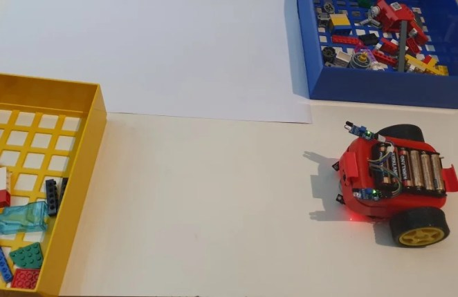 Lunchbox robot in our colour-controlled test area. The robot's camera sees which colour wall is in front of it. The robot uses this information to choose which way to turn