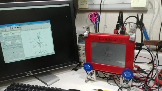 A standard Etch-A-Sketch toy is able to display whatever image is outputted via the bCNC program installed on Raspberry Pi