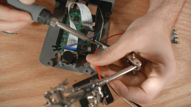 Before attaching Raspberry Pi to the case, Aaron plugged the mic into a USB port. He then connected the camera and speaker, with solder applied to the power wires
