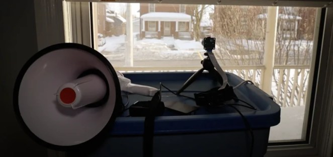 Raspberry Pi camera pointing out of a window connected to a megaphone which will announce when a dog passes by