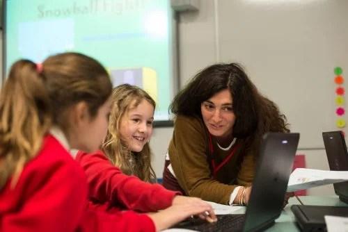 A teacher aids children in the classroom