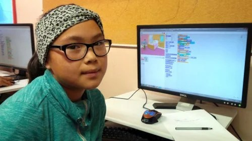 A girl with her Scratch coding project on a desktop computer.