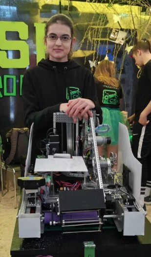 A young woman with a robot she has built.