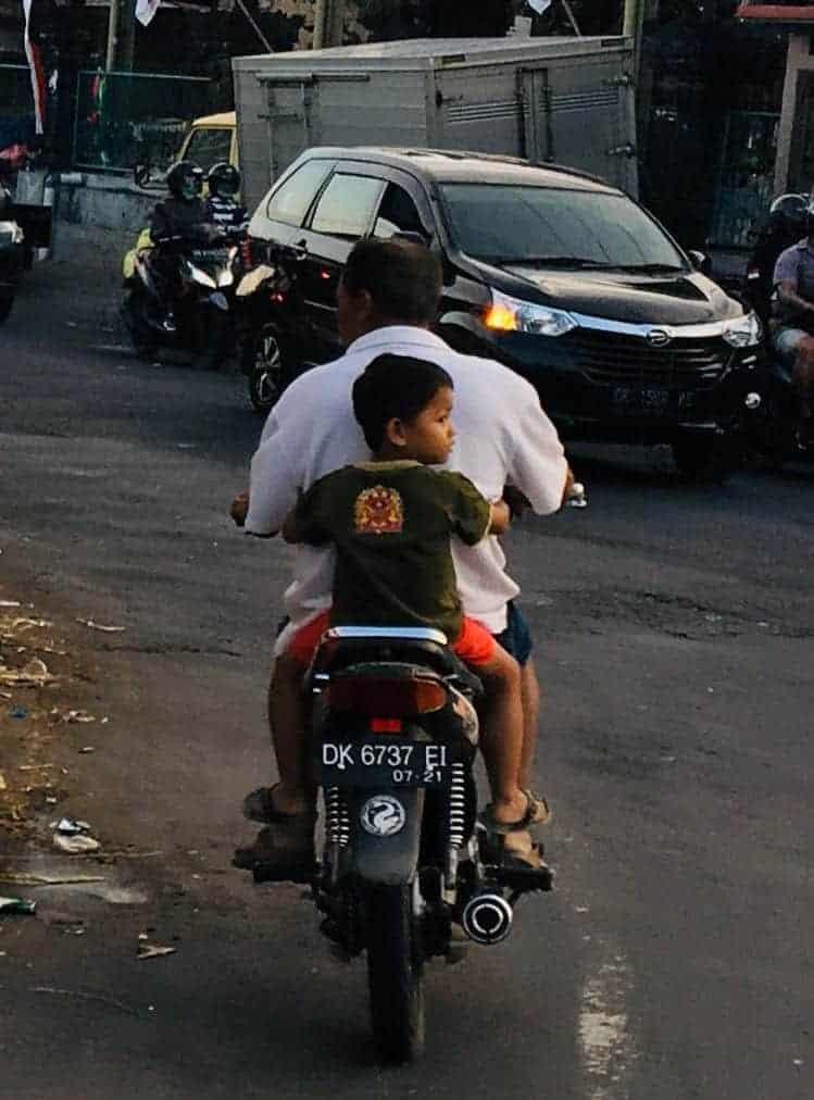 Man and boy on motorbike in Bali