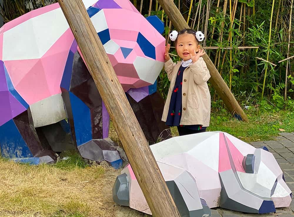 Chinese toddler with panda sculptures at Panda Base