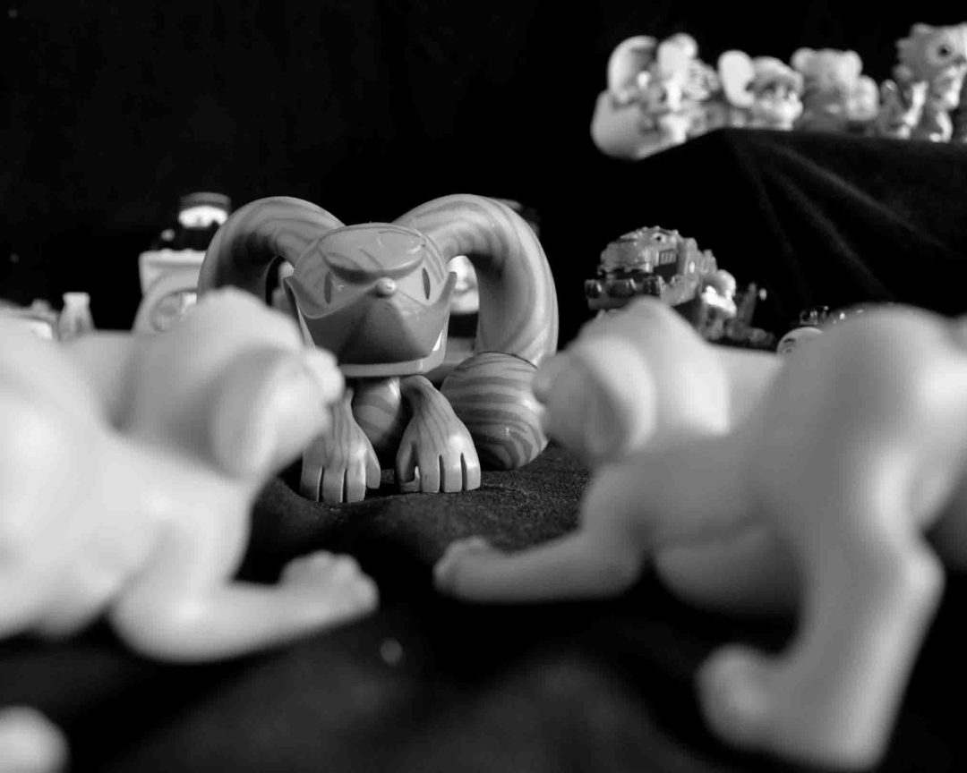 two toy sambas gearing up to fight a mean looking toy in black and white