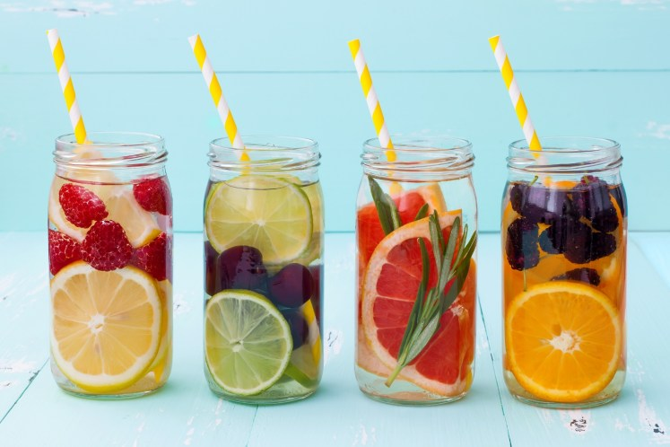 fruit in glasses of water with yellow paper straws