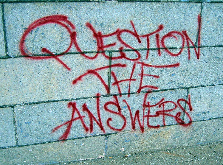 Graffitti on a wall reads 'QUESTION THE ANSWERS'