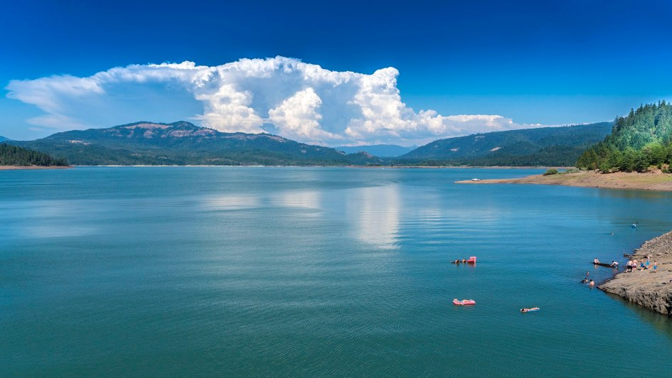 Sun shine on a lake, with fluffy white clouds and picturesque mountains in the distance