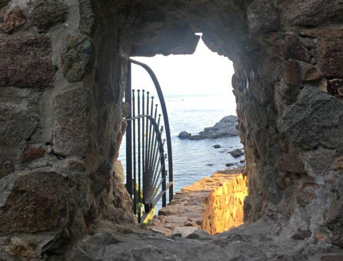 Un agujero en la muralla con vistas a la playa del Codolar de Tossa